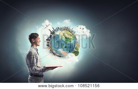 Young man with opened book in hands. Elements of this image are furnished by NASA
