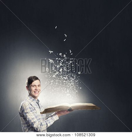 Young student guy with opened book in hands