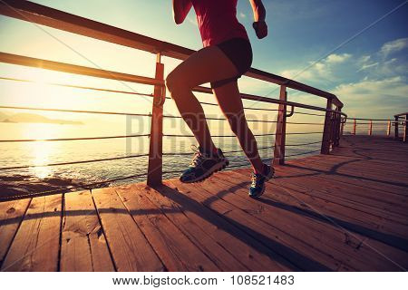 fitness young woman runner running on boardwalk