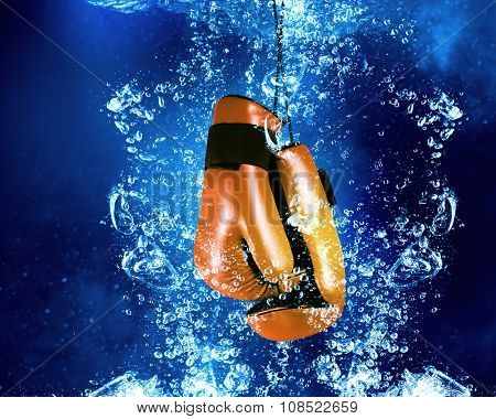 Boxing gloves sinking in clear blue water
