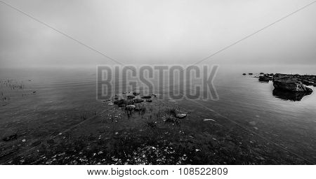 Rocks along the shore in fog obscured vanishing horizon