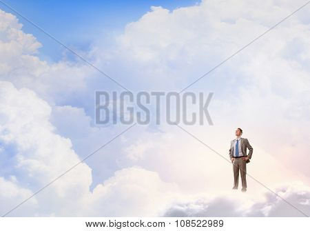Young confident businessman with arms on waist standing on cloud