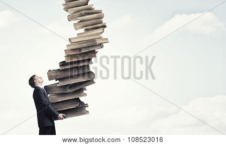 Young businessman carrying stack of old books in his hands