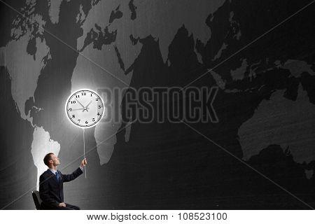 Businessman with clock balloon on dark background