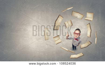 Top view of cute schoolboy in red glasses with finger up