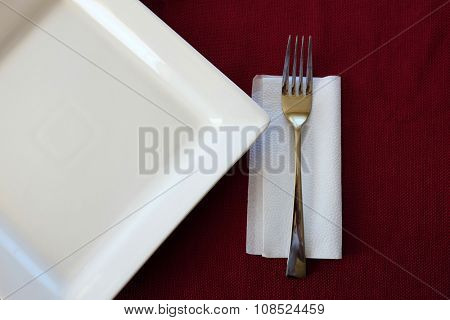 Fork silverware with white plate on red background dinner setting