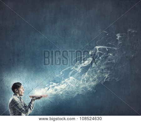 Young man with opened book in hands blowing on pages