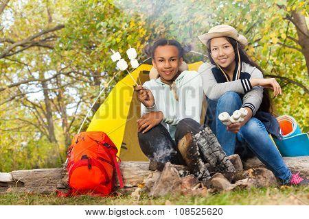 Girls hold marshmallow sticks near fireplace