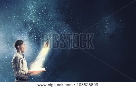Young shocked man with glowing book in hands and hero flying out of pages