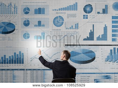 Back view of businessman working with virtual panel