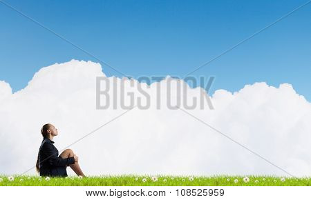 Bored young businesswoman sitting alone on green grass