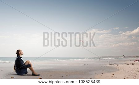 Thoughtful young businesswoman sitting alone on ocean coast