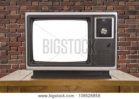 Old television with cut out screen and brick wall.