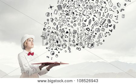 Young woman in white cylinder and red bowtie with book in hands