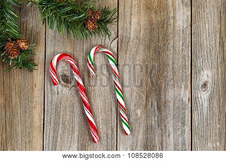 Large Candy Canes And Evergreen Branch On Rustic Wooded Boards
