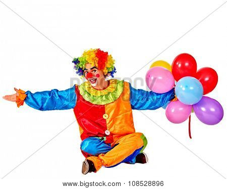 Happy birthday clown holding a bunch of balloons sitting on floor.  Isolated.