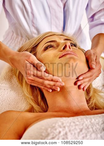 Woman middle-aged take face and neck massage in spa salon.