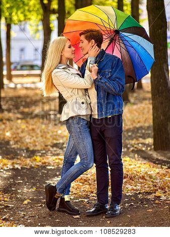 Happy young couple full height embracing under umbrella in autumn day.