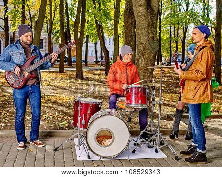 Music street men performers on park autumn outdoor.