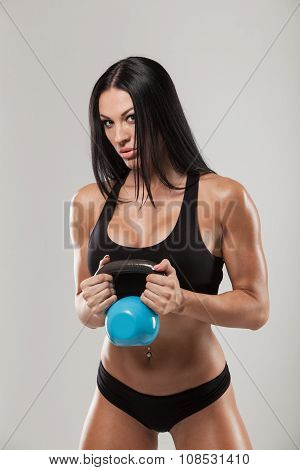 Fitness woman exercising crossfit holding kettlebell strength training biceps. Beautiful fitness ins