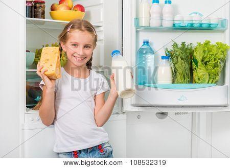 little girl holding cheese and milk near opened fridge