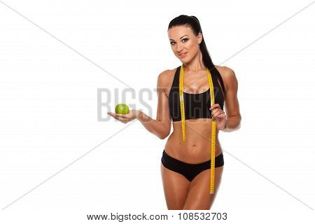 Sporty woman waist with measure tape and green apple isolated on white