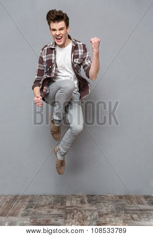 Positive delighted cheerful carefree casual young man in plaid shirt and gray pants jumping in the air and smiling