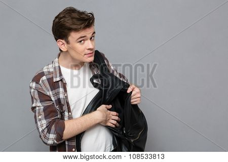 Portrait of a young male student pulls out something of backpack over gray background