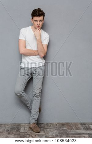 Full length portrait of thoughtful handsome young guy in white t-shirt and gray pants standing on gray background