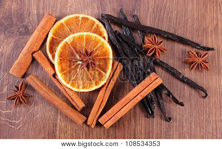 Fragrant Vanilla, Cinnamon, Star Anise And Dried Orange On Wooden Surface
