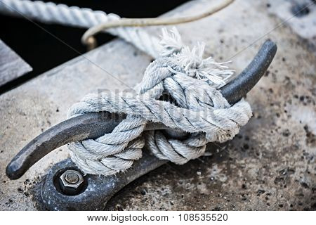 Nautical rope tied around horn cleat on dock, close up.  Key West harbor, Florida.