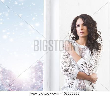 Young and beautiful brunette woman being alone near the window watching first snow falling.