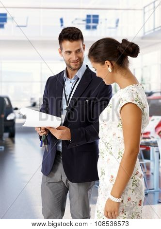 Satisfied caucasian young salesman wearing suit at new car dealership saloon with keys and business papers. Standing, looking at happy female customer.