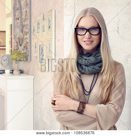 Attractive caucasian casual young classy blonde interior designer wearing glasses at vintage home. Standing, smiling, arms crossed, looking at camera.