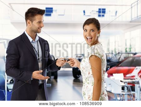 Excited attractive young caucasian lady is getting keys for new car from salesman at car dealership business saloon. Handsome man wearing suit and attractive woman, standing, looking at camera,