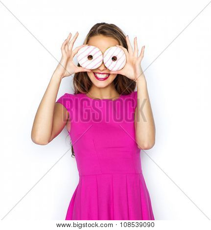 people, holidays, junk food and fast food concept - happy young woman or teen girl in pink dress having fun and looking through donuts