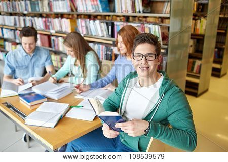 people, knowledge, education and school concept - group of happy students reading books and preparing to exam in library