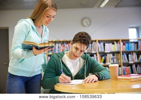 people, knowledge, education and school concept - happy students with book preparing to exams in library