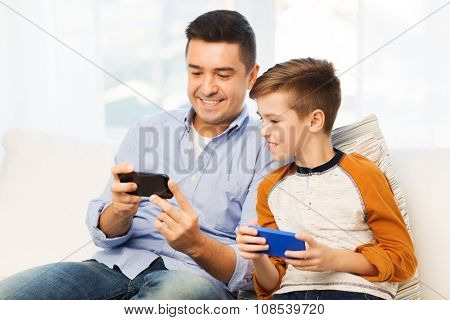 leisure, technology, technology, family and people concept - happy father and son with smartphones texting message or playing game at home