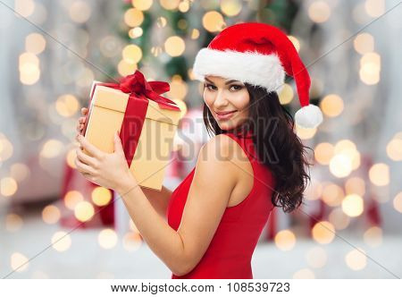 people, holidays, christmas and celebration concept - beautiful sexy woman in red dress and santa hat with gift box over christmas tree lights and presents background