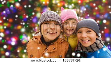 childhood, leisure, friendship and people concept - group of happy kids hugging over snow background and lights