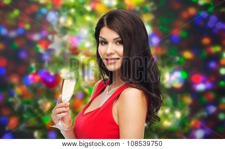 people, holidays, christmas and celebration concept - beautiful sexy woman in red dress with champagne glass over party lights background