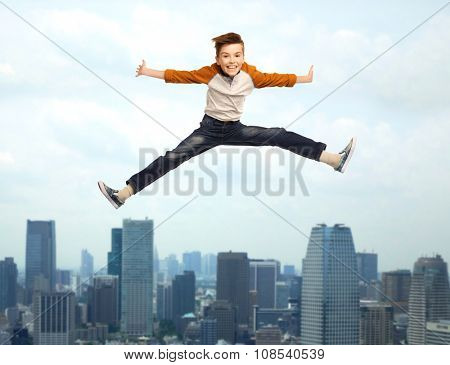 happiness, childhood, freedom, movement and people concept - happy smiling boy jumping in air over city background