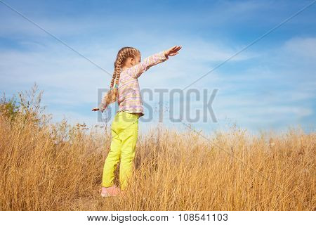 Little Girl In Bright Clothes Standing Against The Sky