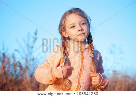Portrait Of A Girl With Pigtails Outdoors