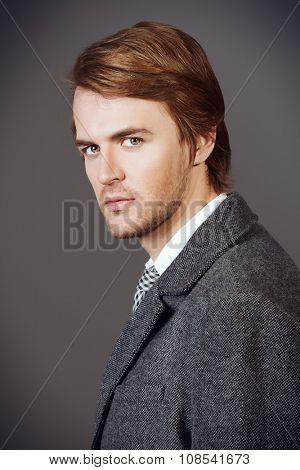 Close-up portrait of a handsome man in an elegant coat. Beauty, fashion. Studio shot.