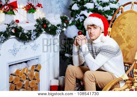 Happy young man celebrating winter holidays at home beautifully decorated for Christmas.