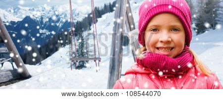 childhood, winter holidays, vacation and people concept - happy beautiful little girl portrait over swing and snowy mountains background
