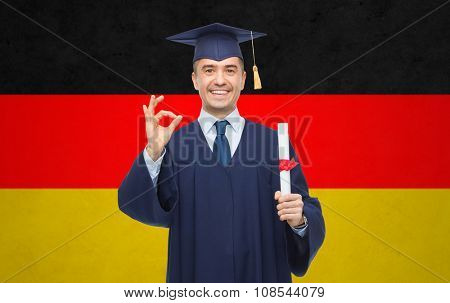 education, graduation, gesture and people concept - smiling adult student in mortarboard with diploma showing ok hand sign over german flag background
