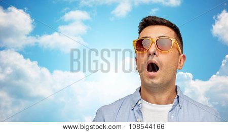 summer, emotions, style and people concept - face of scared or surprised middle aged latin man in shirt and sunglasses over blue sky and clouds background